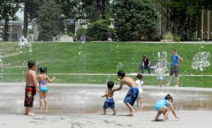 Children playing in water fountain